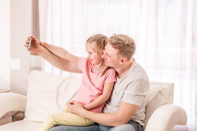 De vader en het jonge geitje nemen selfie in woonkamer royalty-vrije stock foto