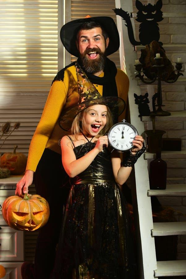 De vader en het meisje vieren Halloween Meisje met wekker en vader op Halloween-vooravond Zijn tijd aan stock afbeelding