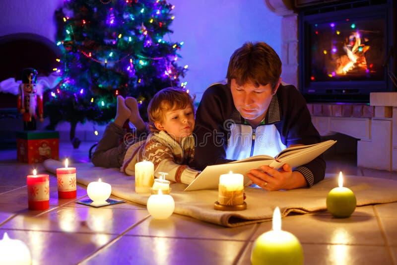 De vader en leuk weinig lezing van de peuterjongen boekt door schoorsteen, kaarsen en open haard stock afbeeldingen