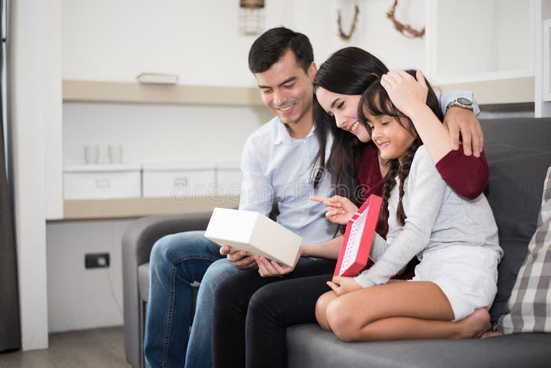 De vader en de moeder verrassen hun dochter door gift of nieuw stuk speelgoed De ouders en de kinderen zijn gelukkig samen in hui royalty-vrije stock foto