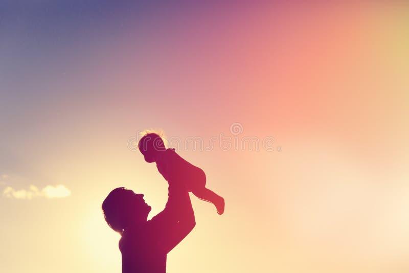 De vader en weinig baby silhouetteren spel bij hemel stock foto's