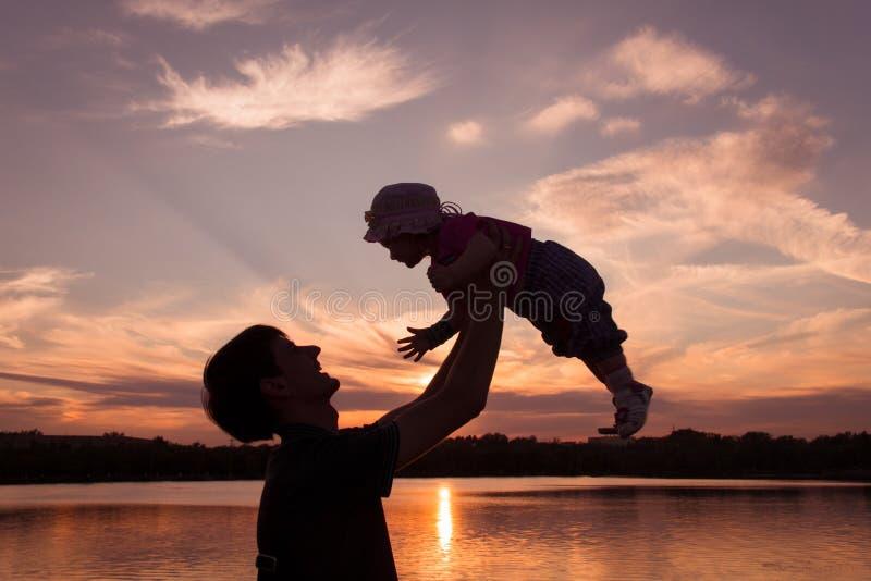 De vader en weinig dochter silhouetteren bij zonsondergang royalty-vrije stock afbeeldingen