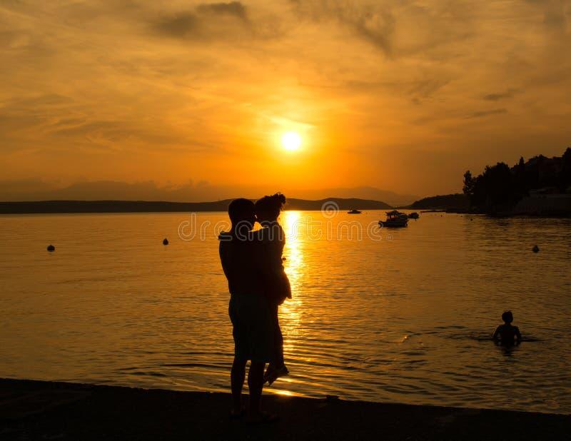 De vader en weinig dochter silhouetteren op het strand stock fotografie