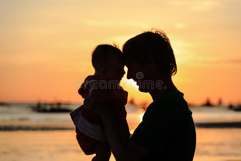 De vader en weinig dochter silhouetteren op zonsondergangstrand royalty-vrije stock foto's
