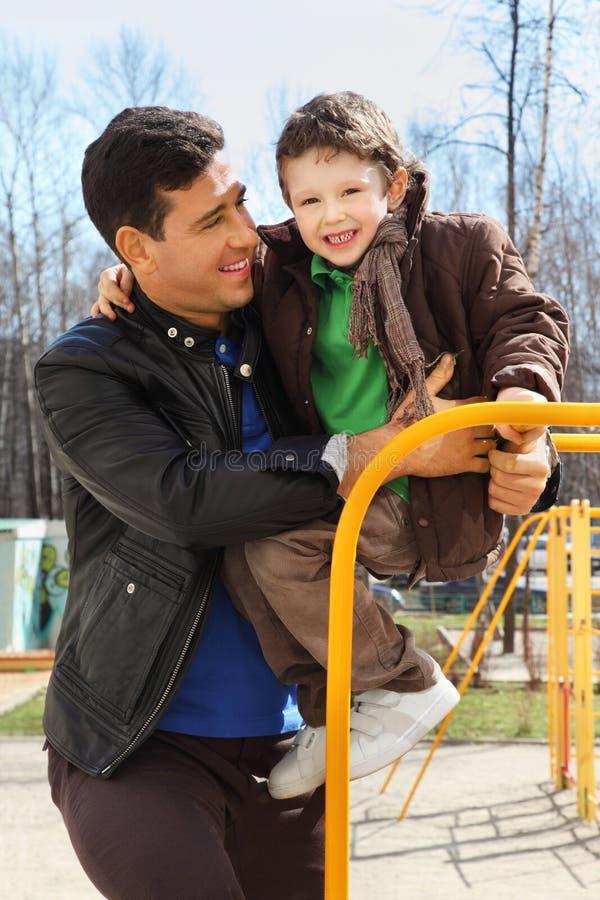 De vader en weinig zoon spelen bij speelplaats stock foto's