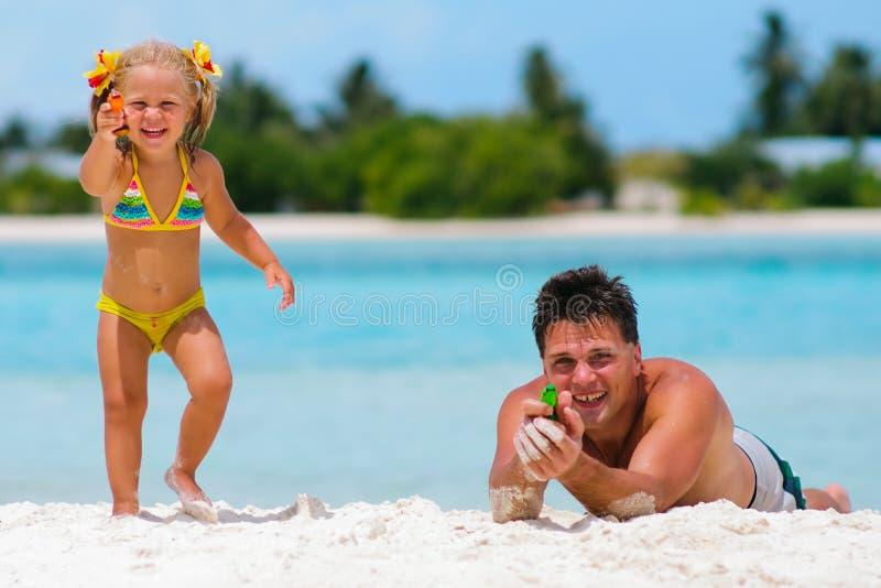 De vader en zijn dochter hebben een pret op exotisch strand stock fotografie