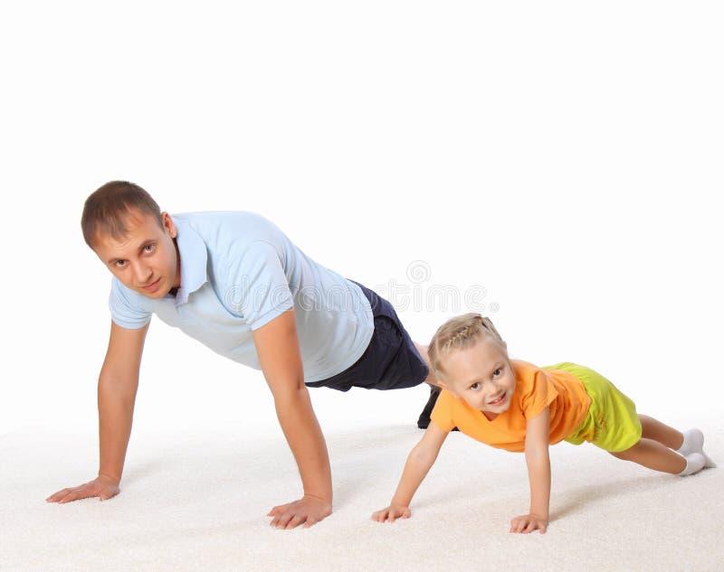 De vader en zijn kleine dochter die oefeningen doen stock fotografie
