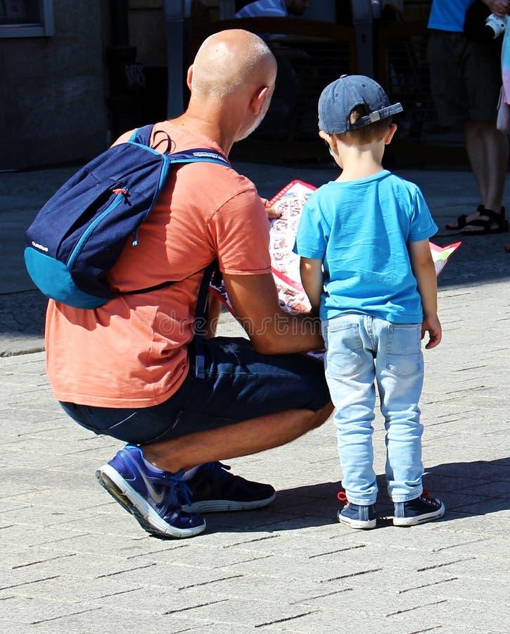 De vader en zijn kleine zoon letten op de kaart royalty-vrije stock afbeeldingen