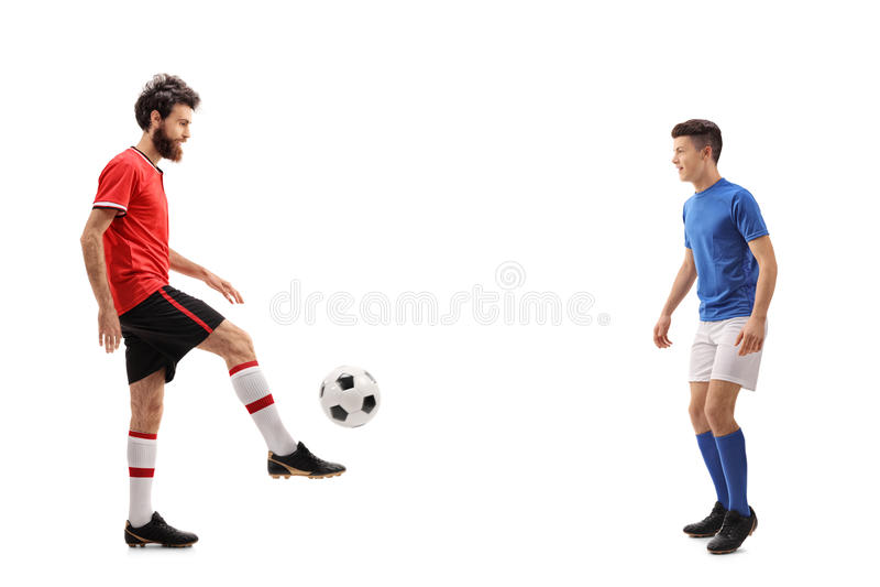 De vader en zijn zoon kleedden zich in jerseys die een voetbal overgaan royalty-vrije stock afbeelding