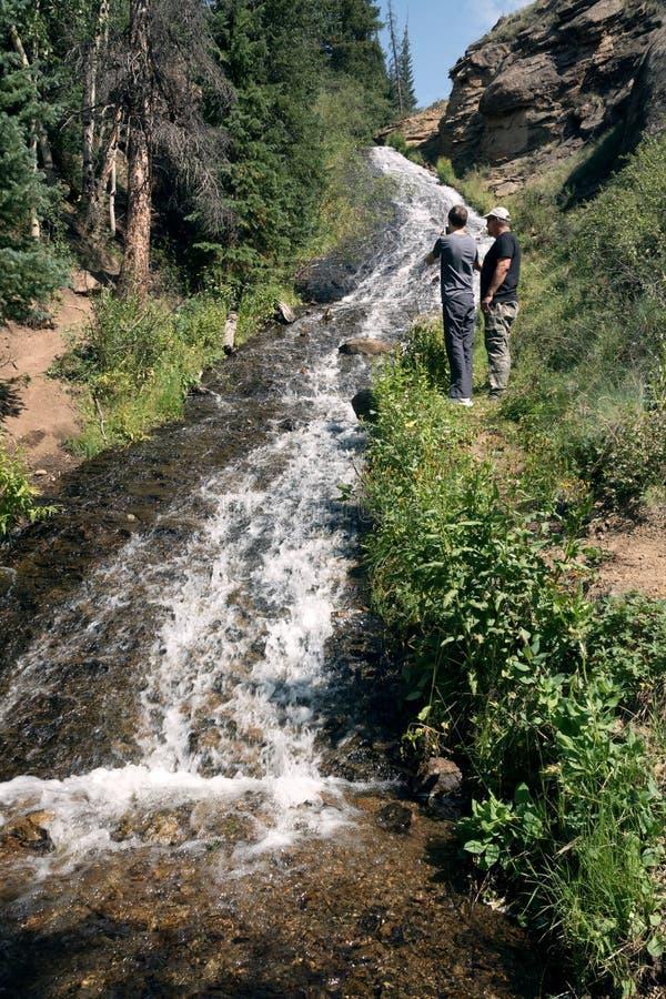De vader en de zoon bekijken de waterval Rex Falls Rio Grande Nati stock foto