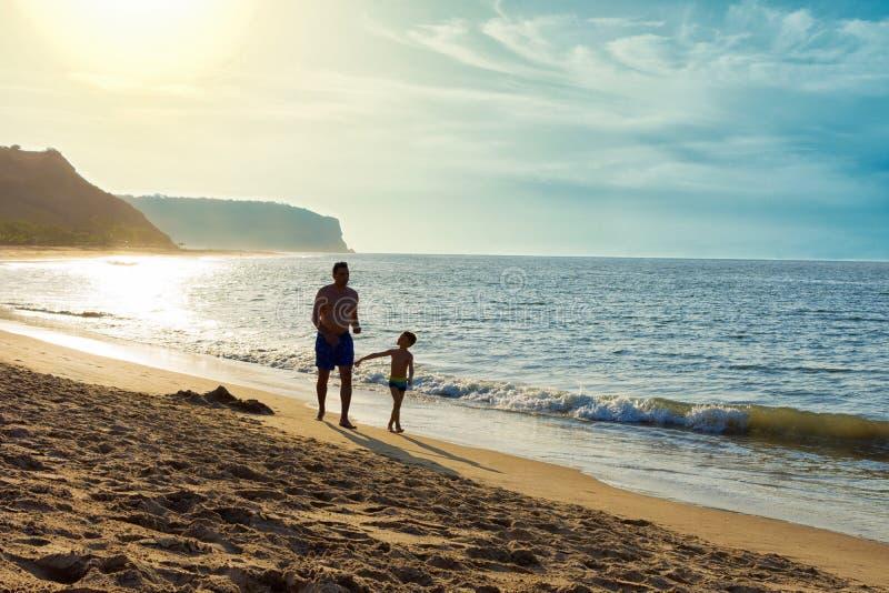 De vader en de zoon genieten van doorbrengend samen tijd in gesprek bij het zandstrand met overzees, hemel en bergen op de achter royalty-vrije stock foto's