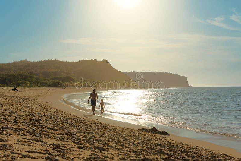De vader en de zoon genieten van doorbrengend samen tijd in gesprek lopend bij het zandstrand op hete de zomerdag royalty-vrije stock afbeeldingen