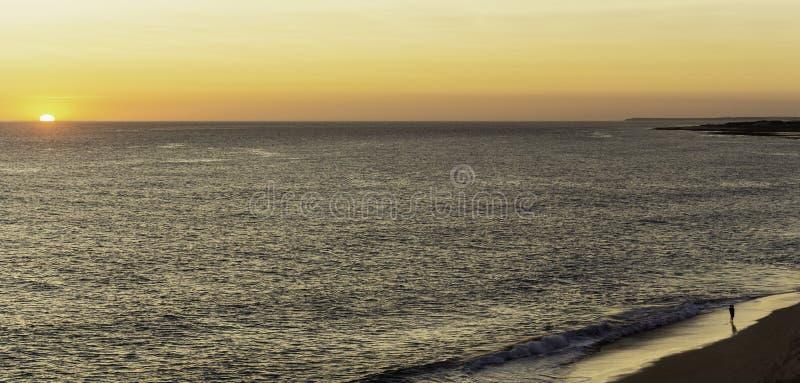 De vader en de zoon letten op de zonsondergang bij de rand van het overzees, op het strand stock afbeelding