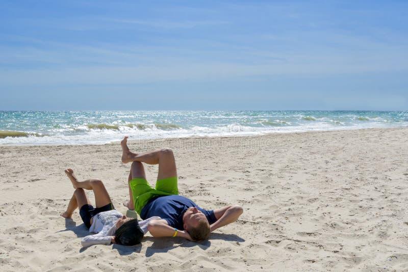 De vader en de zoon ontspannen op het strand stock afbeelding