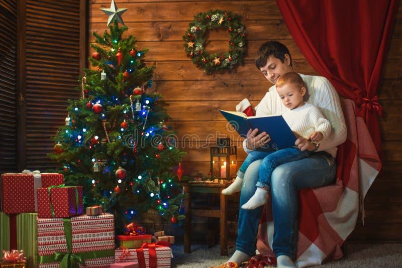 De vader en de zoon vieren Kerstmis in een verfraaid huis stock foto