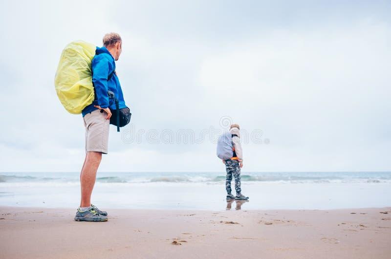 De vader en de zoonsverblijf van Backpackerreizigers op oceaandesretstrand stock afbeelding