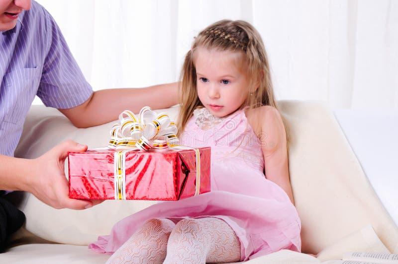 De vader geeft zijn jonge dochter stock foto