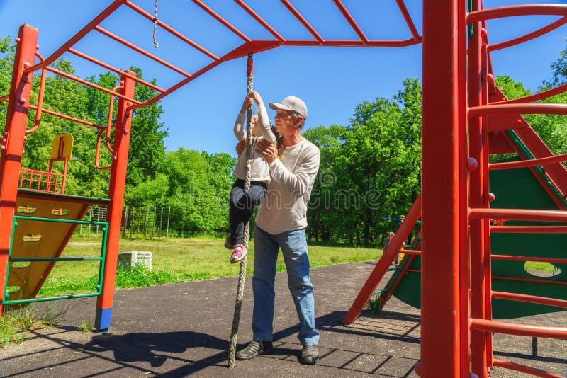 De vader helpt de dochter van zijn kind om de kabel te beklimmen Concept het helpen van jongeren royalty-vrije stock foto's