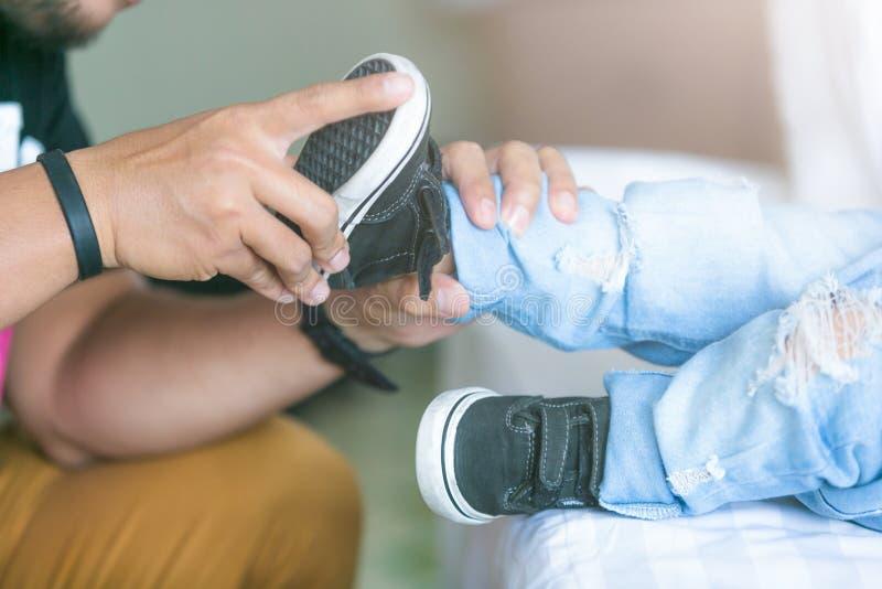 De vader helpt zijn zoon om zijn schoenen in de ruimte op bed te binden stock foto