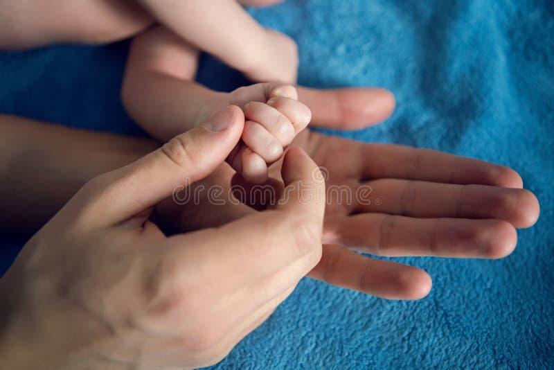 De vader houdt de hand van zijn babyzoon royalty-vrije stock fotografie