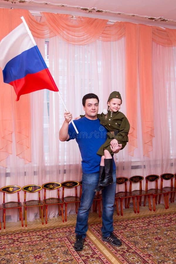 De vader houdt dochter in zijn wapens en golvende vlag stock foto