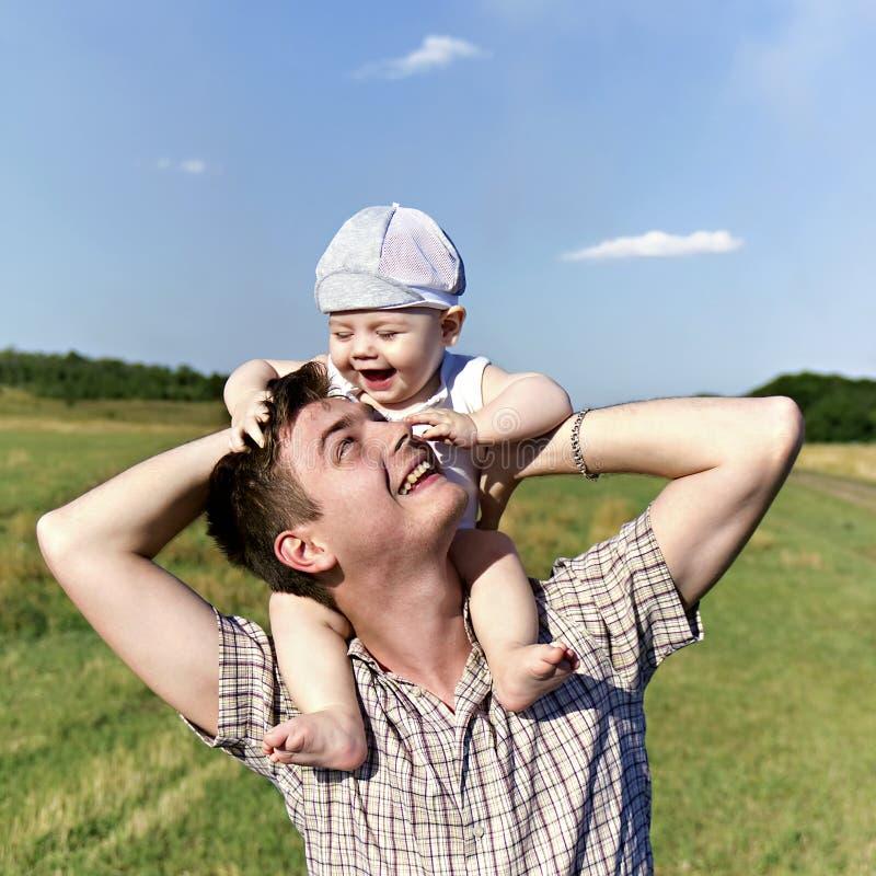 De vader houdt een klein kind op zijn schouders stock afbeeldingen