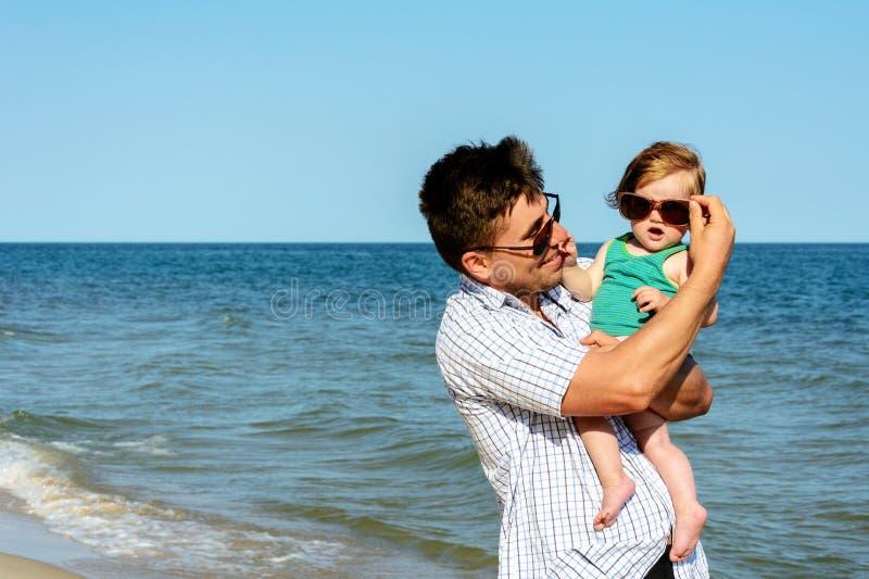 De vader houdt een kleine dochter op zijn schouders in zonnebril royalty-vrije stock afbeelding