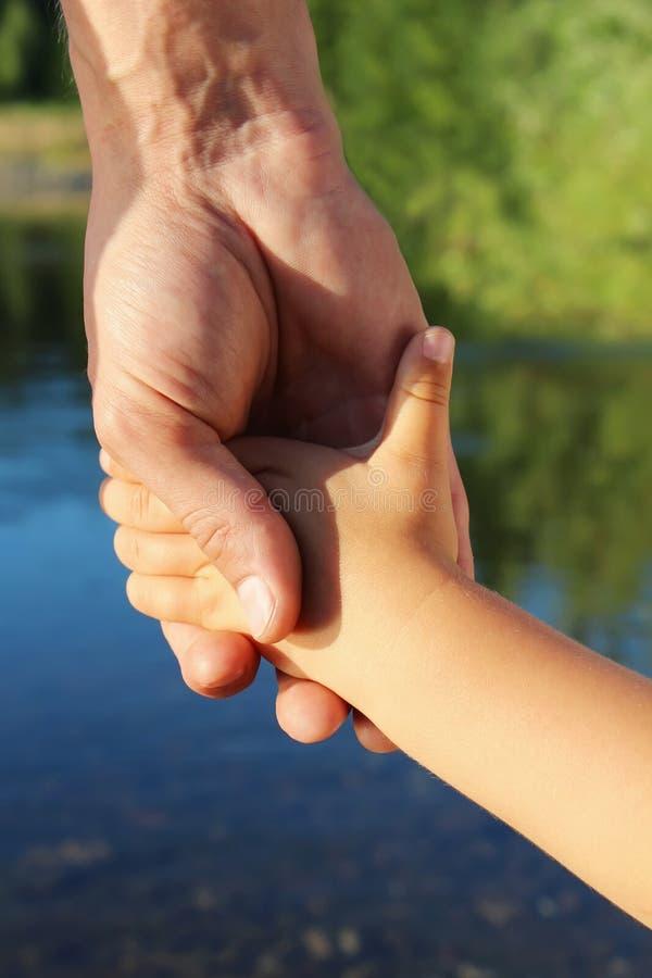 De vader houdt het kind door een hand op gang royalty-vrije stock afbeelding