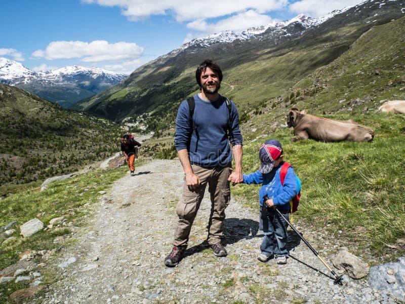 De vader houdt zijn zoon door de hand tijdens een stijging in de bergen royalty-vrije stock foto
