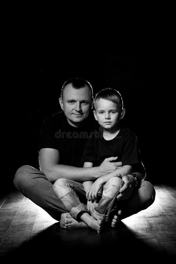 De vader houdt zoon in zijn wapens en koestert hem De mens en de jongen zitten samen tegen een zwarte achtergrond Gelukkig vaders royalty-vrije stock afbeelding