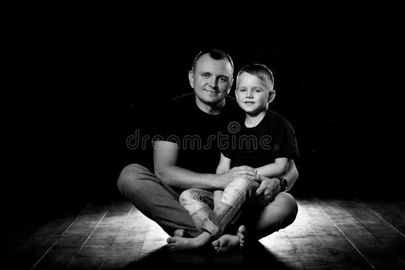 De vader houdt zoon in zijn wapens en koestert hem De mens en de jongen zitten samen tegen een zwarte achtergrond Gelukkig vaders royalty-vrije stock afbeeldingen