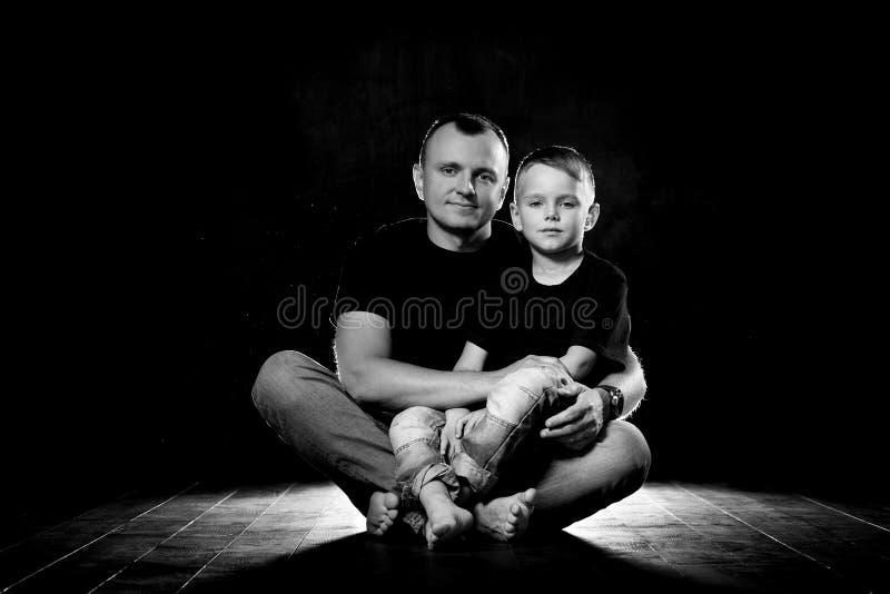 De vader houdt zoon in zijn wapens en koestert hem De mens en de jongen zitten samen tegen een zwarte achtergrond Gelukkig vaders stock afbeeldingen