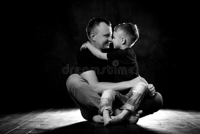 De vader houdt zoon in zijn wapens en koestert hem De mens en de jongen zitten samen tegen een zwarte achtergrond Gelukkig vaders stock fotografie