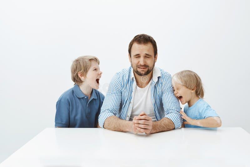 De vader kan geen energieke zonen met slecht gedrag behandelen Papazitting bij lijst en het schreeuwen van wanhopig gevoel terwij royalty-vrije stock fotografie