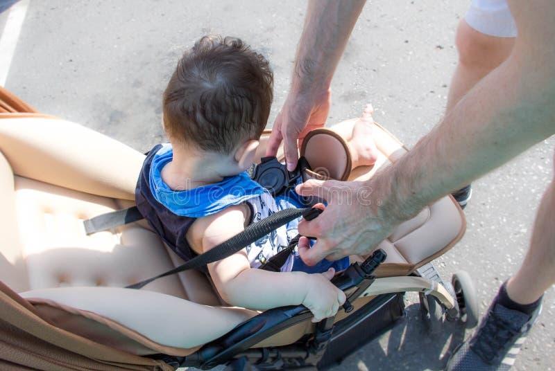 De vader loopt met de baby in de wandelwagen Ouderschap en vaderschap op zwangerschapsverloven de baby van de vaderriem in de wan royalty-vrije stock fotografie