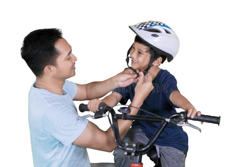 De vader maakt een helm aan zijn zoon op studio vast stock foto