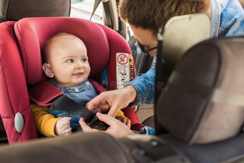 De vader maakt zijn baby in autozetel vast royalty-vrije stock foto