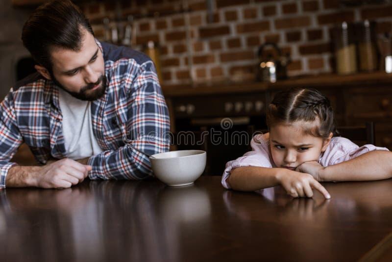 de vader met dochterzitting bij lijst, weinig jong geitje wil niet eet ontbijt royalty-vrije stock foto's