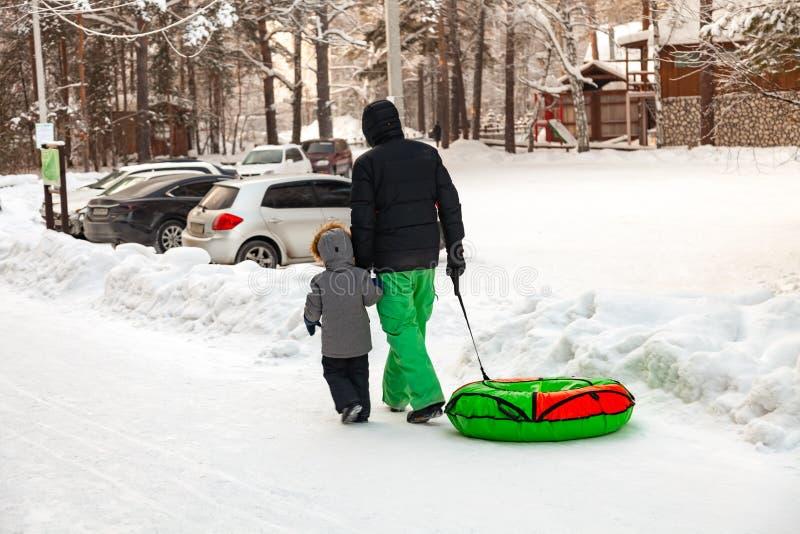 De vader met een kind in de winterkostuums gaat onderaan de heuvel met een broodje voor het berijden in de sneeuw in de handen na royalty-vrije stock fotografie