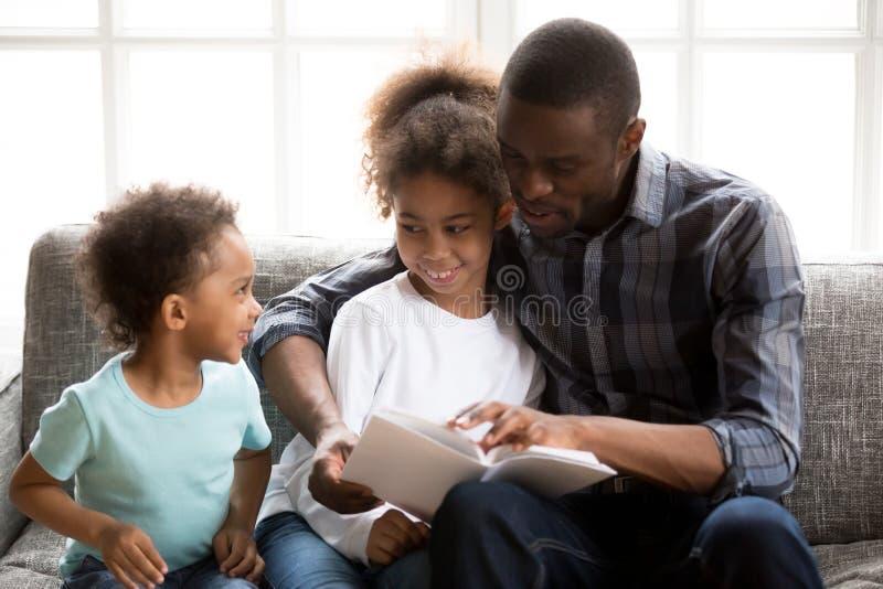 De vader met kinderen las thuis een boek royalty-vrije stock afbeelding