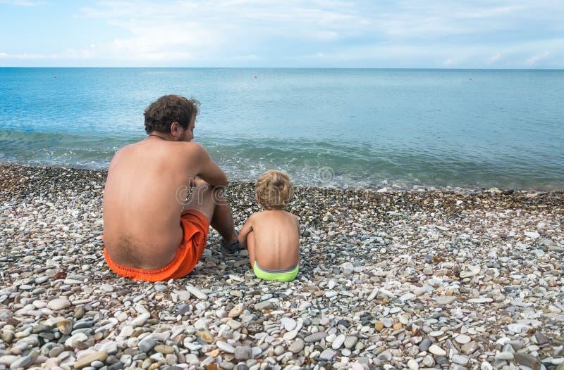 De vader met kleine zoon zit bij het overzees royalty-vrije stock foto