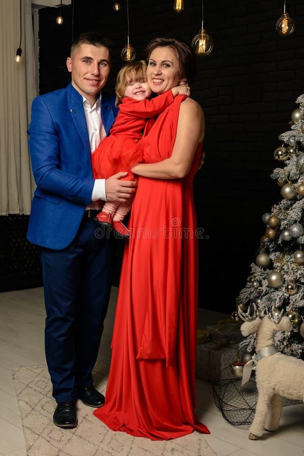 De vader met moeder en hun dochter die zich naast een Kerstboommamma bevinden met dochter in rood kleedt zich stock afbeelding