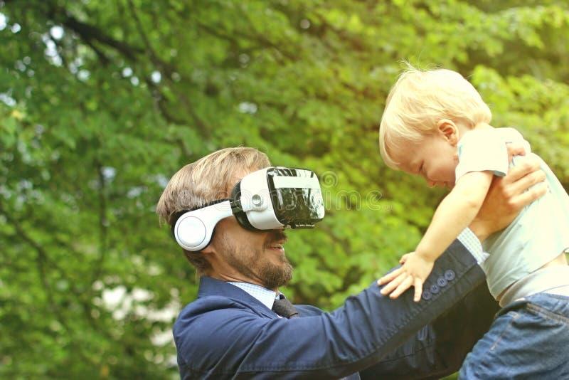 De vader met virtuele glazen houdt een kind in zijn handen fut stock afbeeldingen