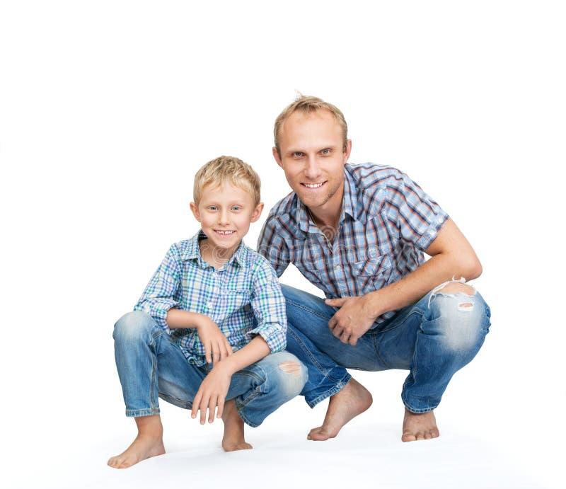 De vader met zoon kleedde zich in jeans en plaidoverhemden op het wit royalty-vrije stock afbeeldingen