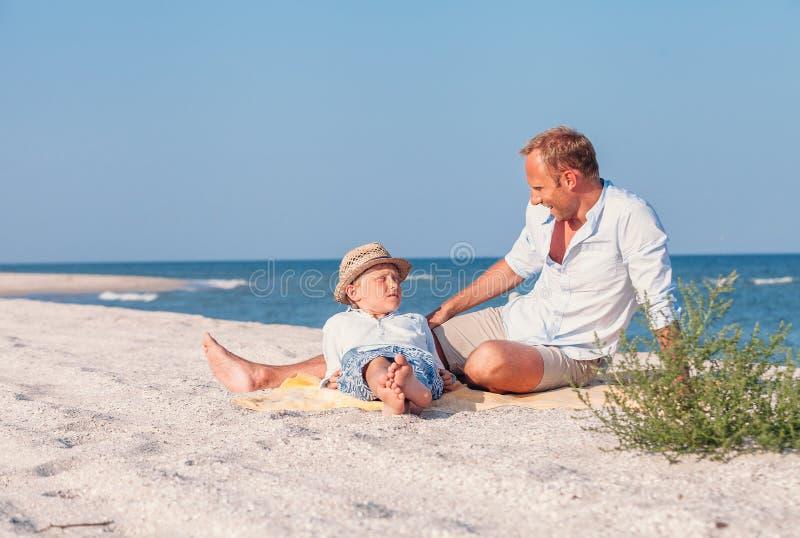 De vader met zoon neemt een zonbad op het overzeese strand stock foto's