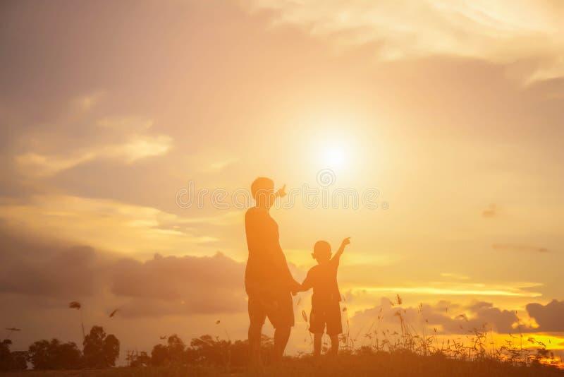 De vader nam de baby leert om bij zonsondergang te lopen royalty-vrije stock afbeelding