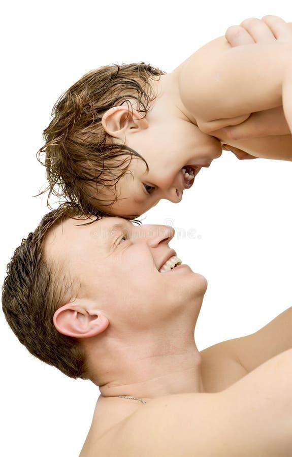 De vader neemt zijn babyjongen uit het geïsoleerde bad stock foto's