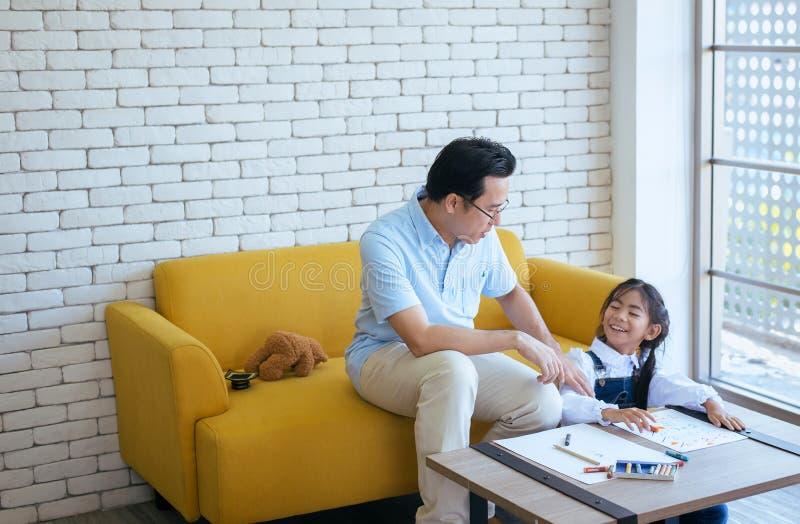 De vader onderwijst jong meisjeskind om thuiswerk samen, Gelukkig en pret, Familieliefde te doen royalty-vrije stock afbeeldingen