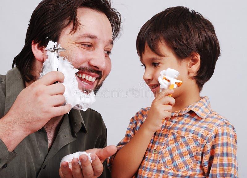De vader onderwijst zijn jongen hoe te te scheren stock foto