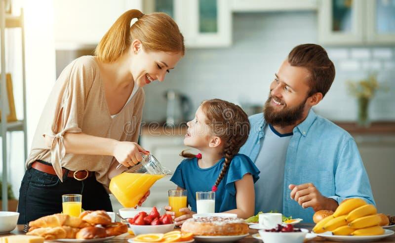 De vader van de familiemoeder en de kinddochter hebben Ontbijt in keuken in ochtend stock afbeeldingen